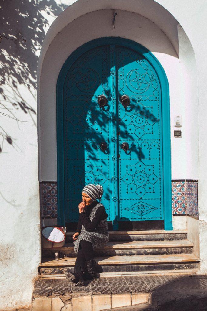 Lépcsőn ülő idős nő Sidi Bou Saidban.